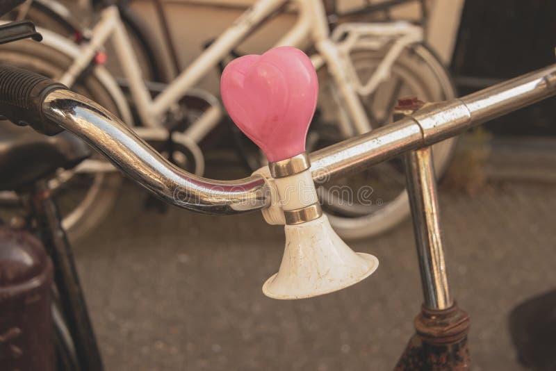Chiuda su della campana della bicicletta come cuore sui manubri fotografia stock