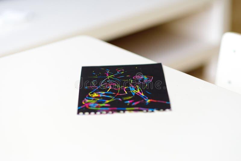 Chiuda su della carta magica della pittura del graffio sulla tavola bianca a casa immagini stock