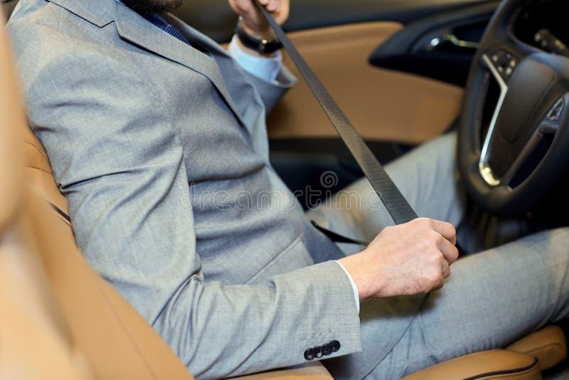 Chiuda su della cintura di sicurezza del sedile della legatura dell'uomo in automobile fotografie stock libere da diritti
