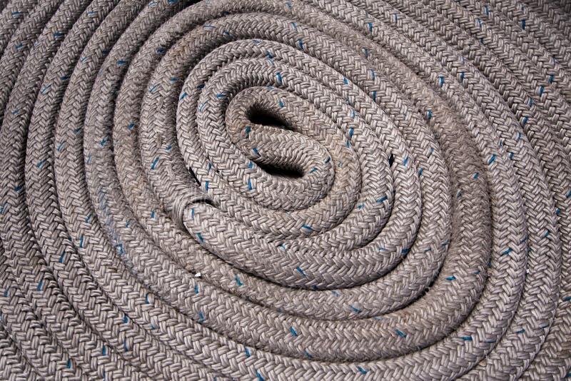 Chiuda su della corda nautica grigia arrotolata e con i punti culminanti blu fotografia stock libera da diritti