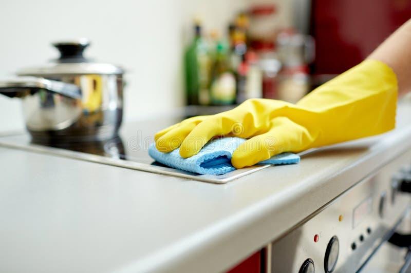 Chiuda su della cucina del fornello di pulizia della donna a casa fotografia stock