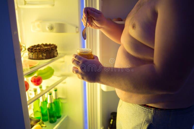 Chiuda su della dieta grassa della rottura dell'uomo alla notte e mangi il dolce non sano fotografia stock libera da diritti