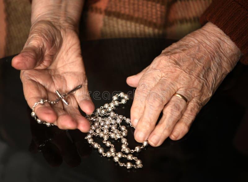 Chiuda su della donna anziana che prega con il rosario d'argento con l'incrocio fotografia stock