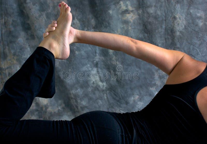 Chiuda in su della donna che fa la posa mezza di yoga dell'arco fotografie stock