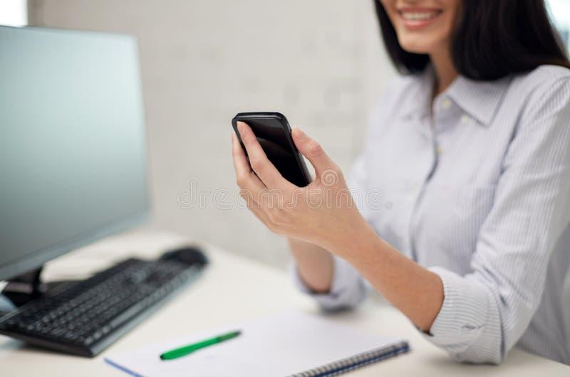 Chiuda su della donna che manda un sms sullo smartphone all'ufficio fotografie stock libere da diritti