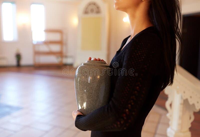 Chiuda su della donna con l'urna di cremazione in chiesa immagini stock
