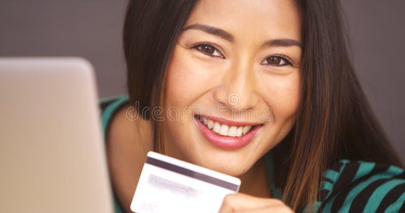 Chiuda su della donna giapponese che sorride con la carta di credito fotografie stock