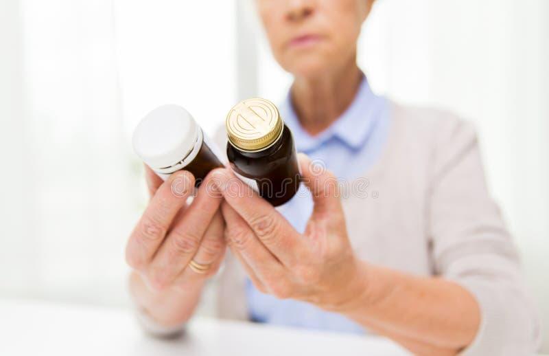 Chiuda su della donna senior con i barattoli della medicina fotografie stock libere da diritti