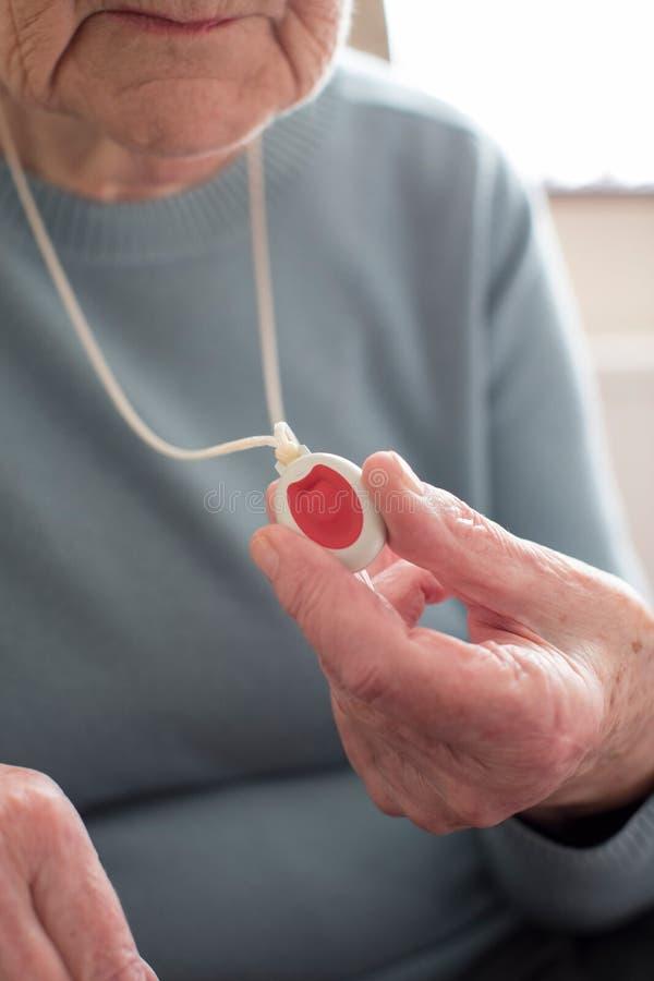 Chiuda su della donna senior indisposta che tiene il bottone personale dell'allarme a fotografia stock libera da diritti