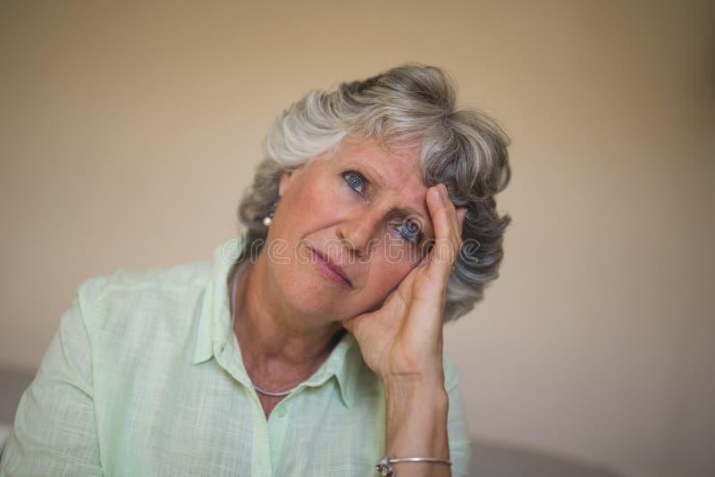 Chiuda su della donna senior premurosa triste a casa fotografie stock