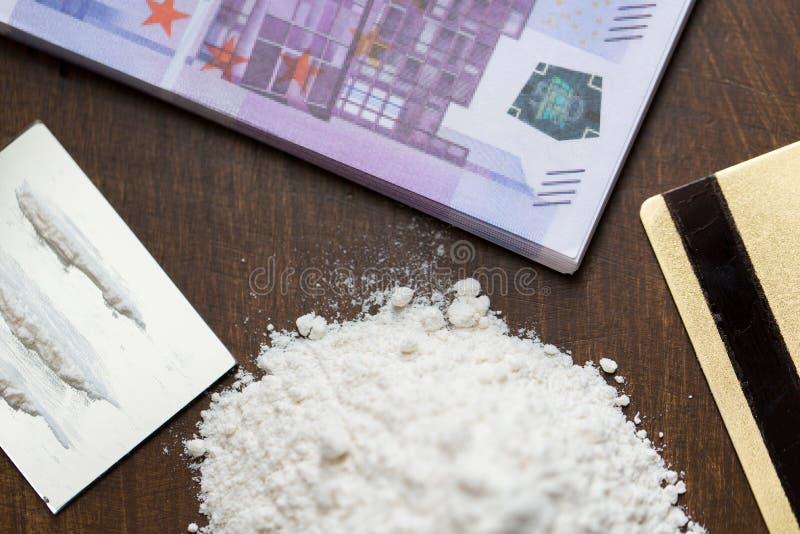 Chiuda su della dose di farmaco e dei soldi del crack fotografie stock