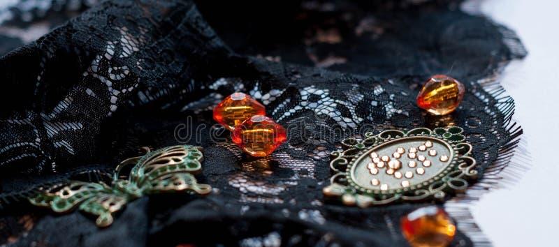 Chiuda su della farfalla verde decorativa, delle perle arancio, del telaio e dei cristalli di rocca su pizzo nero immagine stock