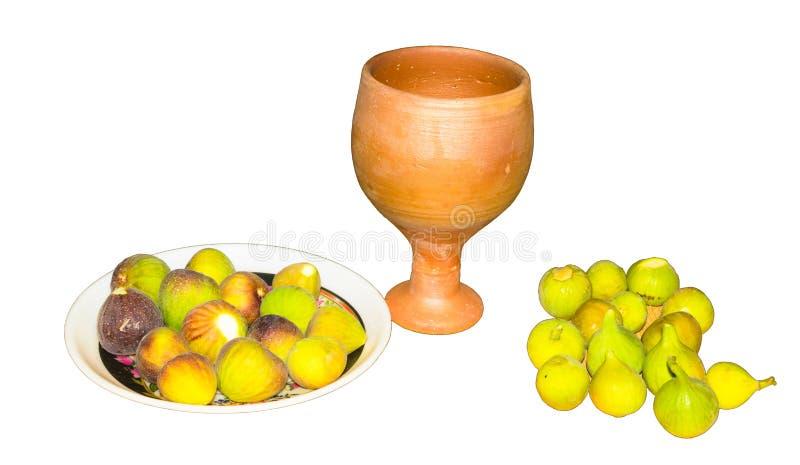 Chiuda su della frutta fresca del fico in un piatto con il vetro dell'argilla isolato fotografia stock libera da diritti