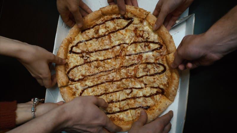 Chiuda su della gente che prende le fette di pizze differenti Il gruppo di multi amici etnici che mangiano la pizza italiana port immagini stock libere da diritti