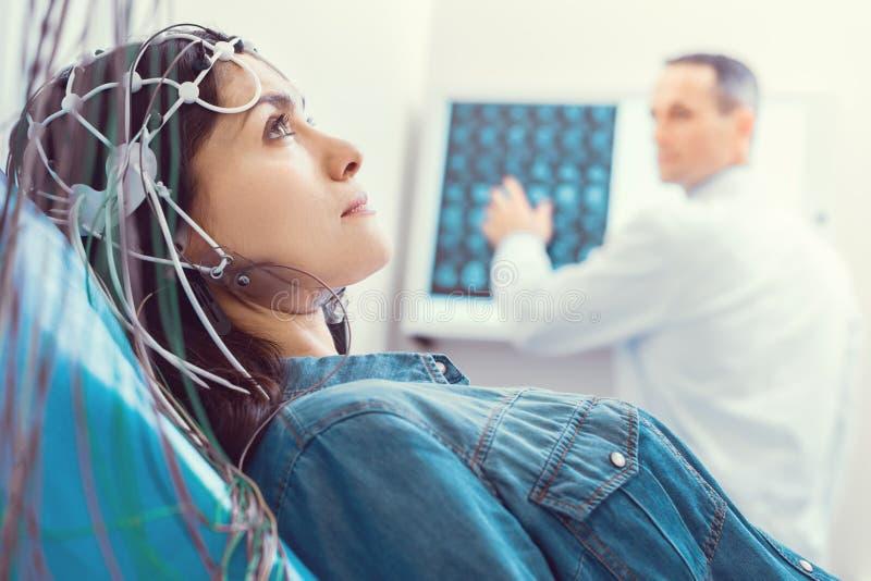 Chiuda su della giovane donna che ottiene il cervello analizzato da elettroencefalografo fotografie stock