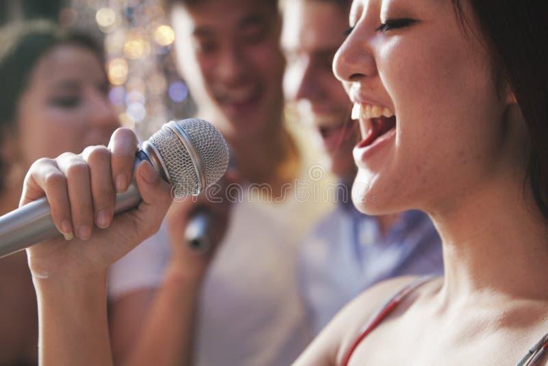 Chiuda su della giovane donna che tiene un microfono e che canta al karaoke, amici che cantano nei precedenti immagini stock libere da diritti