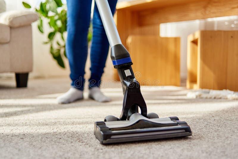 Chiuda su della giovane donna in jeans che puliscono il tappeto con l'aspirapolvere in salone, spazio della copia Lavoro domestic fotografia stock