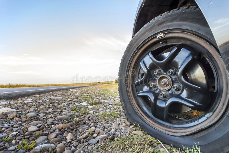 Chiuda su della gomma piana su un'automobile sulla strada della ghiaia fotografia stock