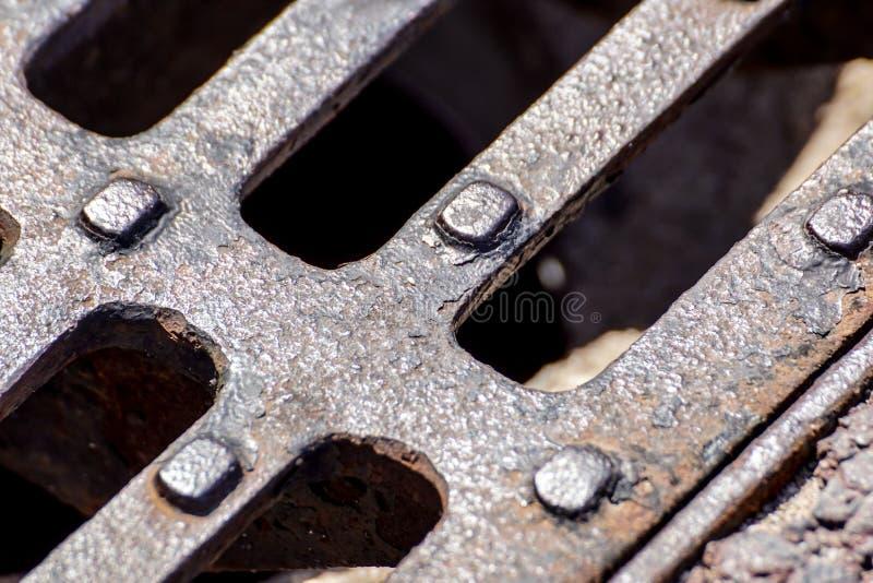 Chiuda su della griglia del metallo della fogna, modello della griglia quadrata, copertura dello scolo della botola in strada cem fotografia stock libera da diritti