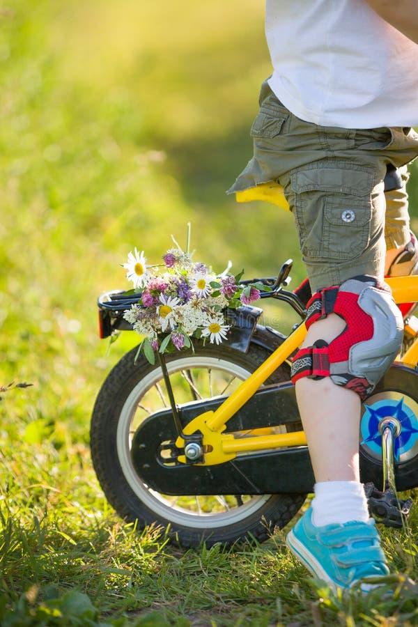 Chiuda su della guida del ragazzo del bambino sulla sua bicicletta con i fiori, all'aperto Ragazzo che guida la sua prima bici gi fotografia stock libera da diritti