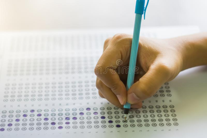 Chiuda su della High School o dello studente universitario che tiene una scrittura della penna sulla carta del modulo di risposta immagine stock libera da diritti