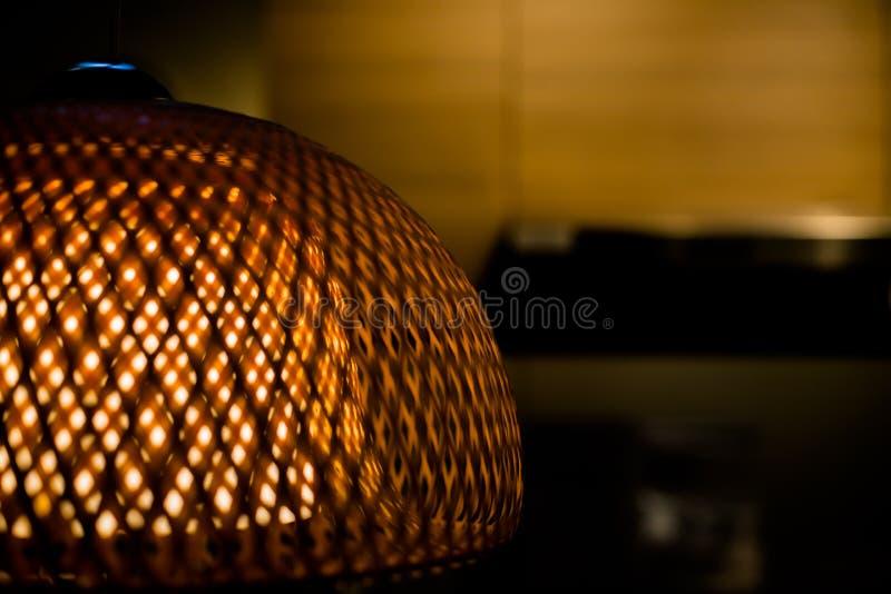 Chiuda su della lampada di bambù tessuta lusso con luce gialla dentro Paralume di vimini Openwork Vecchia lampada di modo Copi lo fotografie stock