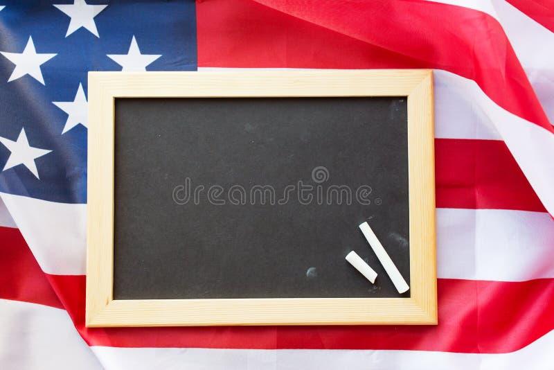 Chiuda su della lavagna della scuola sulla bandiera americana immagine stock libera da diritti