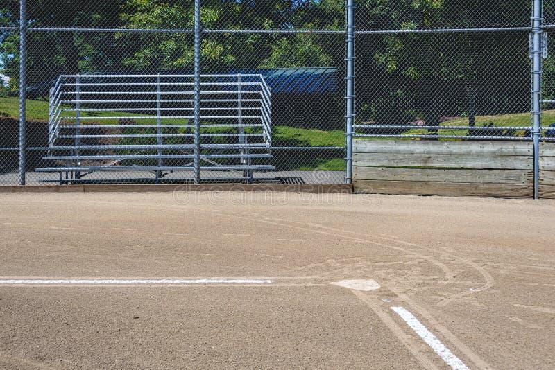 Chiuda su della linea di base di recente segnata che conduce al piatto domestico, con l'arresto e la gradinata, campo di baseball immagini stock libere da diritti