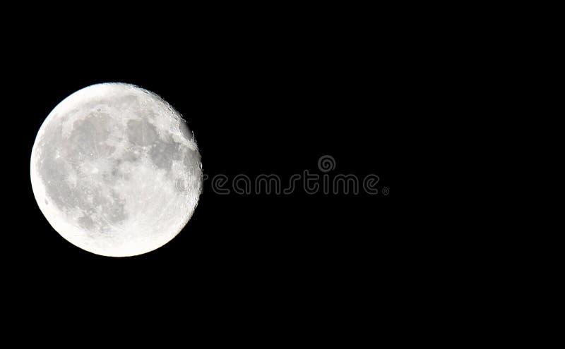 Chiuda su della luna piena con fondo nero sul lato sinistro della foto con lo spazio della copia immagini stock libere da diritti