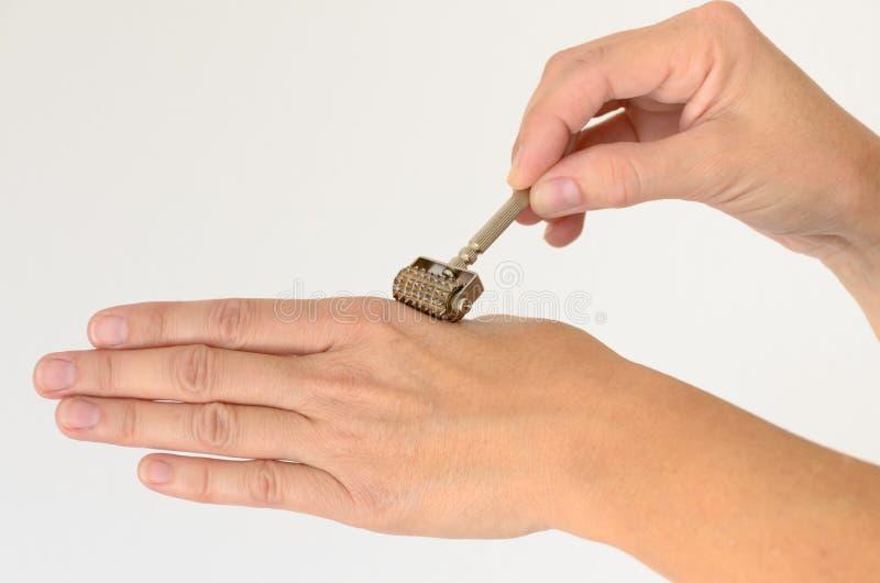 Chiuda su della mano che è massaggiata con il rullo di derma fotografie stock libere da diritti