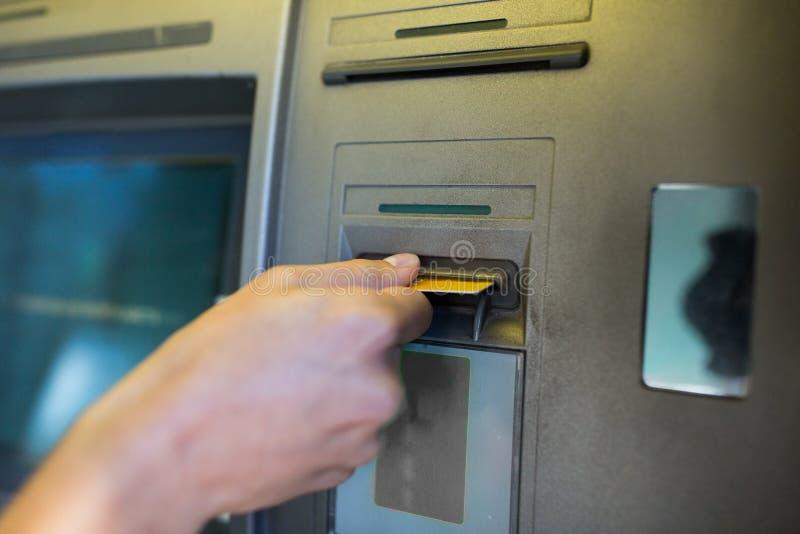 Chiuda su della mano che inserisce la carta alla macchina di bancomat immagine stock