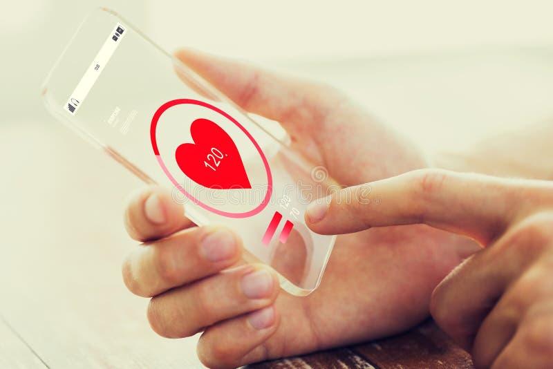 Chiuda su della mano con la frequenza cardiaca sullo smartphone immagini stock libere da diritti