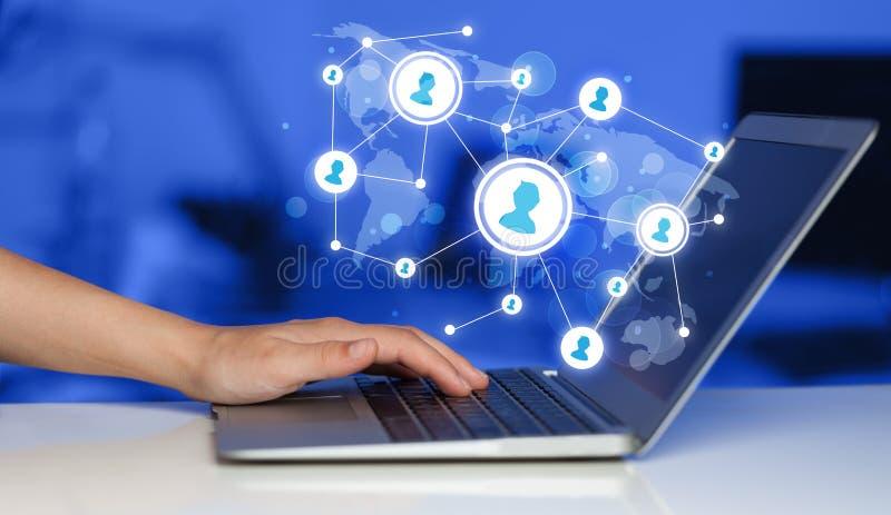 Chiuda su della mano con le icone di media del sociale e del computer portatile fotografia stock libera da diritti