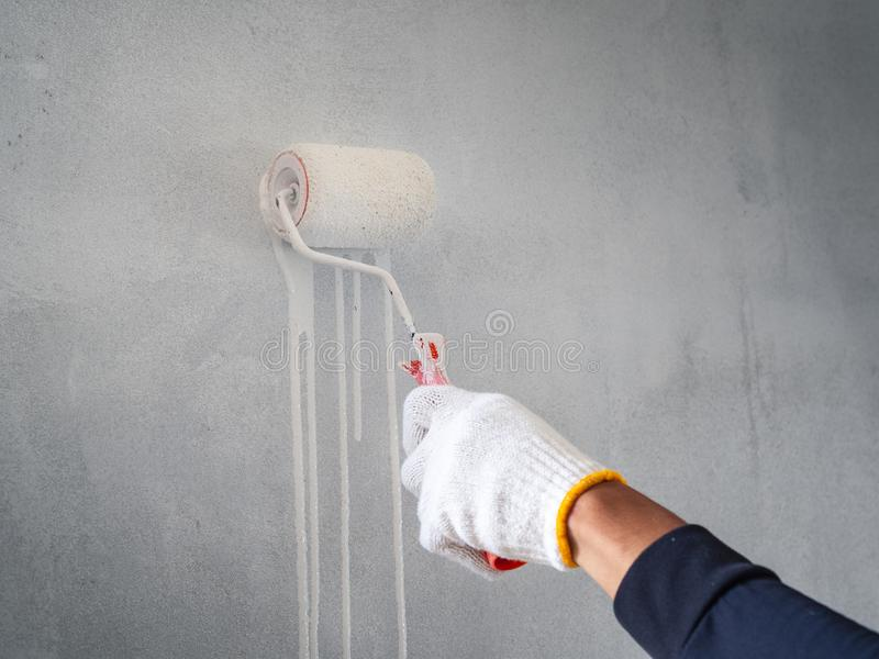 Chiuda su della mano del lavoratore facendo uso del rullo e della spazzola per la parete di verniciatura Concetto della costruzio immagini stock