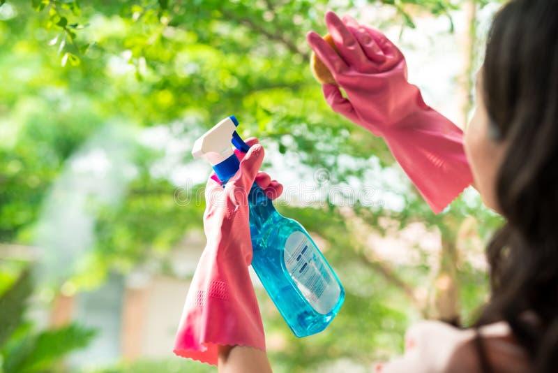 Chiuda su della mano del ` s della donna con la finestra speciale di pulizia dello straccio fotografie stock