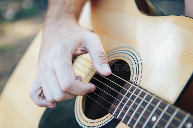 Chiuda su della mano dell'uomo che gioca la chitarra Uomo che gioca chitarra Giocando sulla chitarra acustica all'aperto immagini stock libere da diritti