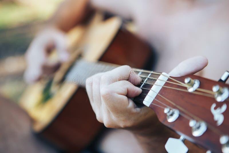Chiuda su della mano dell'uomo che gioca la chitarra Uomo che gioca chitarra Giocando sulla chitarra acustica all'aperto immagine stock libera da diritti