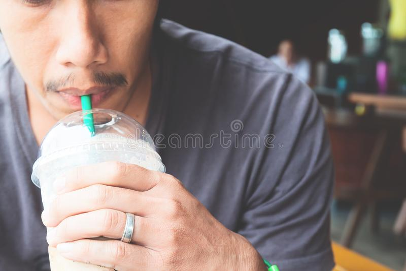 Chiuda su della mano dell'uomo che tiene una tazza di caffè ghiacciato fotografia stock libera da diritti