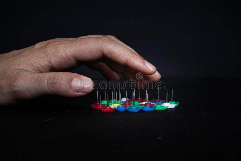 Chiuda su della mano di una donna che si accinge al tocco alcuni aghi con le dita immagini stock
