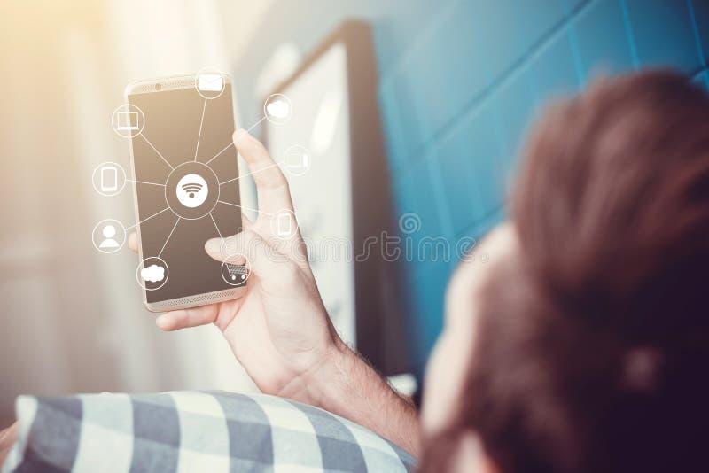 chiuda su della mano facendo uso dello Smart Phone con la rete di comunicazione online immagini stock