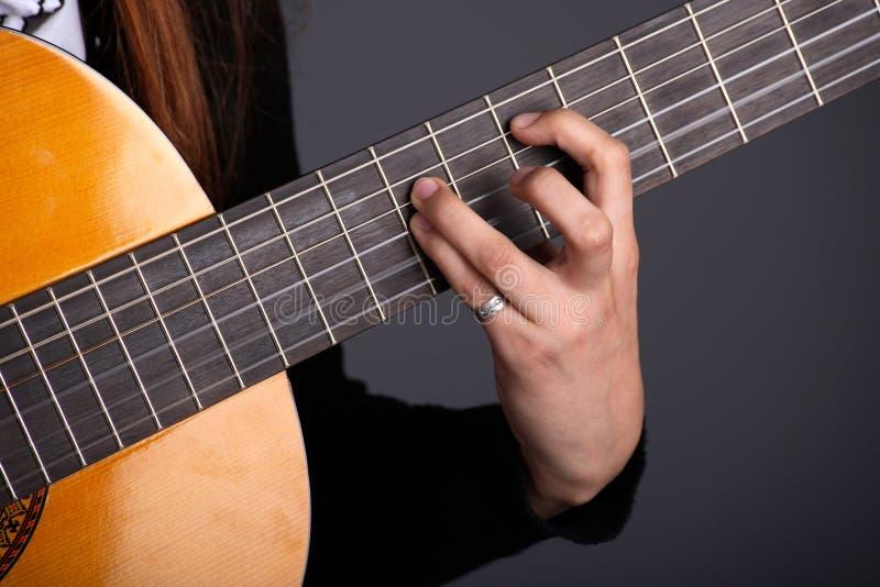 Chiuda in su della mano femminile del chitarrista che gioca la chitarra fotografia stock libera da diritti