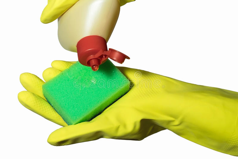 Chiuda su della mano femminile in guanto di gomma protettivo giallo che tiene la spugna verde di pulizia contro il fondo bianco fotografia stock libera da diritti