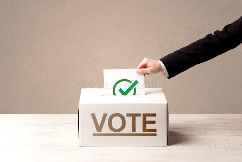 Chiuda su della mano maschio che mette il voto in un'urna immagine stock libera da diritti