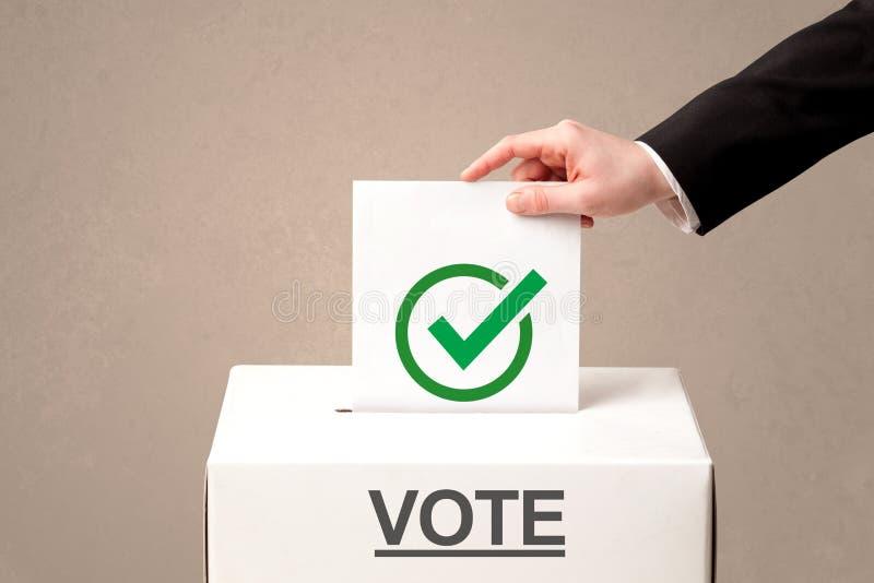 Chiuda su della mano maschio che mette il voto in un'urna immagini stock libere da diritti
