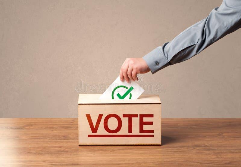 Chiuda su della mano maschio che mette il voto in un'urna fotografie stock