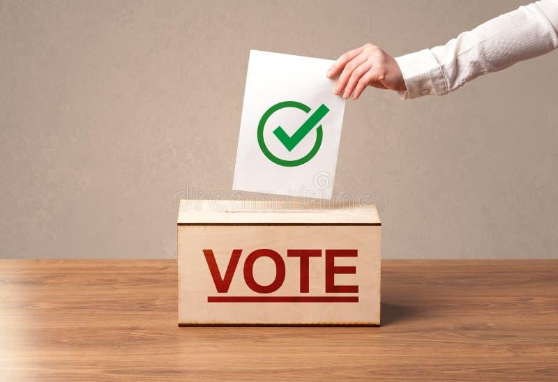 Chiuda su della mano maschio che mette il voto in un'urna fotografie stock libere da diritti