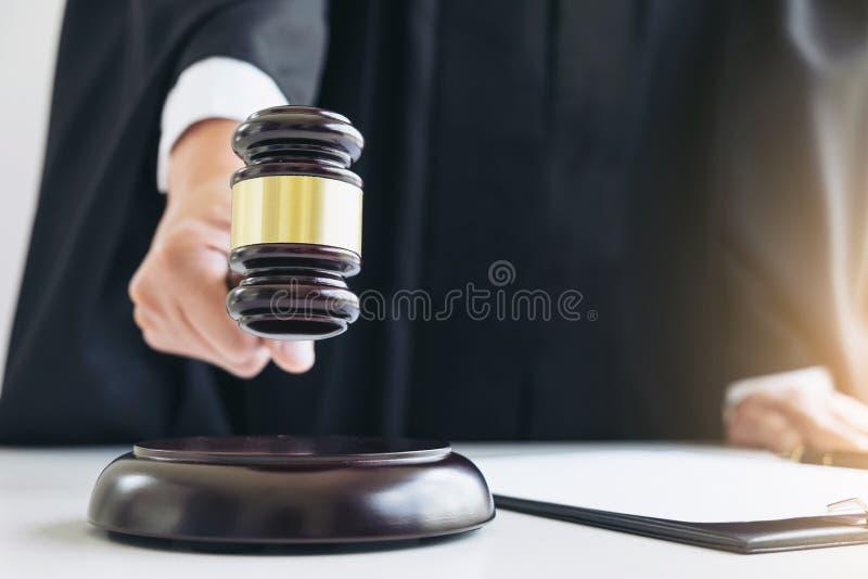 Chiuda su della mano maschio del giudice o dell'avvocato che colpisce il martelletto sopra così fotografia stock