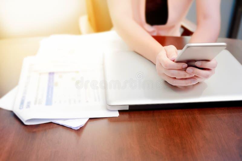 Chiuda su della mano una donna che utilizza lo smartphone mobile sul computer portatile in me fotografia stock