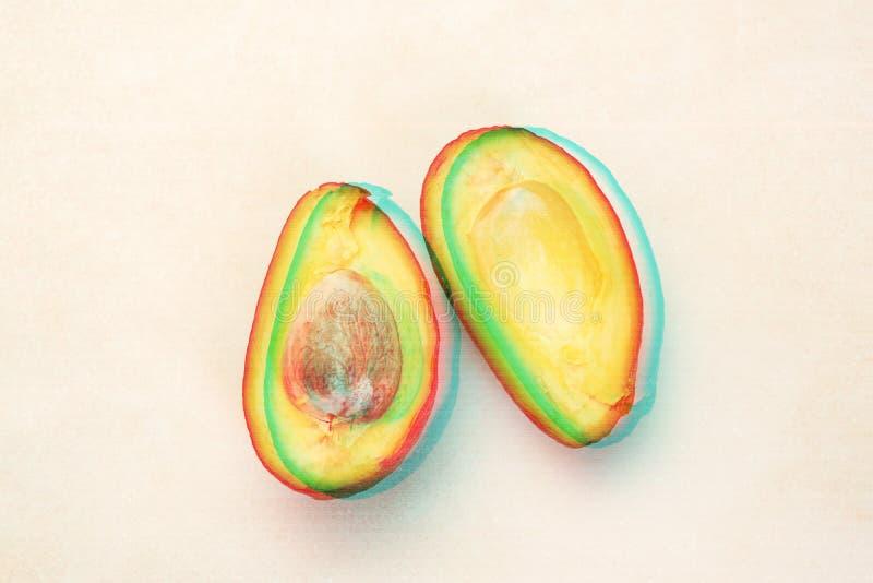 Chiuda su della metà dell'avocado maturo affettato sulla tavola bianca con effetto di impulso errato fotografie stock libere da diritti