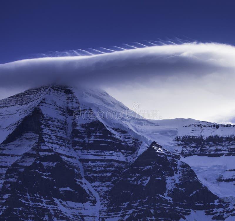 Chiuda su della nuvola sopra la sommità innevata della montagna immagini stock libere da diritti